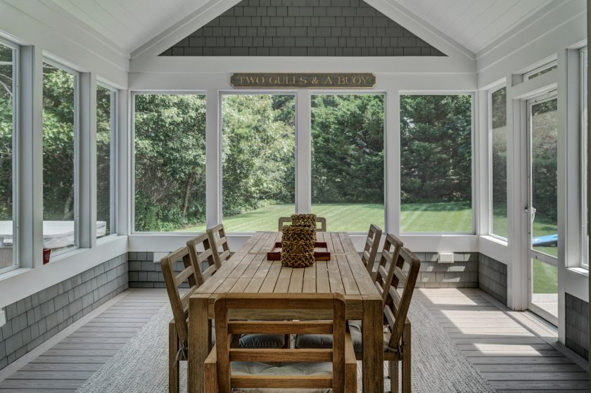 Screened-in porch with dining table and chairs