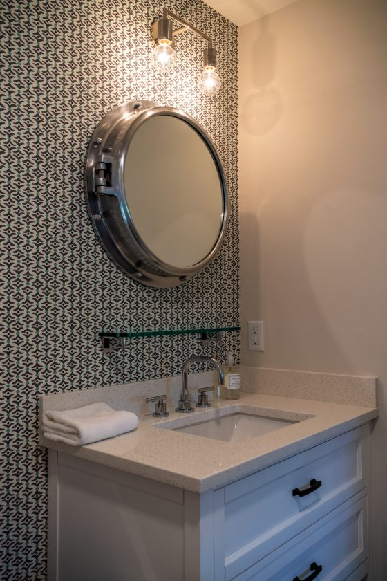Porthole-style mirror above bathroom vanity